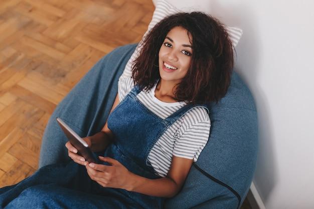 Wewnątrz portret z góry wesoła dziewczyna w dżinsowym kombinezonie relaksująca się na niebieskiej poduszce w weekend