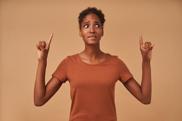Wewnątrz portret zdezorientowanej młodej, ładnej ciemnoskórej kręconej kobiety, gryzącej niepokojąco dolną wargę, patrząc w bok i pokazującą w górę palcami wskazującymi, odizolowany na beżu