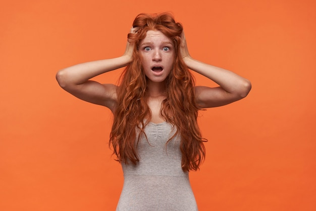 Wewnątrz portret zszokowanej, atrakcyjnej młodej rudowłosej kobiety z falistymi londyńskimi włosami stojącej na pomarańczowym tle, ściskającej głowę z szeroko otwartymi ustami i okrągłymi oczami