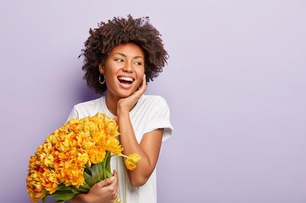 Wewnątrz pozytywna kobieta śmieje się i bawi, rozkoszuje się aromatem wiosennych żółtych tulipanów, nosi zwykłą białą koszulkę, odizolowaną na liliowej ścianie, puste miejsce na treści promocyjne. wiosna