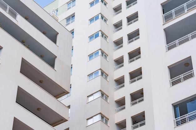 Wewnątrz rogu wielopiętrowego budynku mieszkalnego, bliski widok okien i balkonów.
