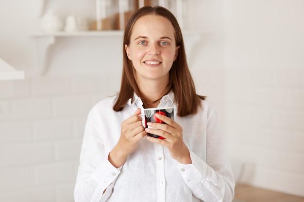Wewnątrz strzał uśmiechający się ładna kobieta filiżankę kawy w kuchni, stojąc z przyjemnym uśmiechem, ciesząc się gorącą herbatą rano po śniadaniu, patrząc na kamerę z pozytywem.