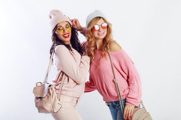 Wewnątrz studio obraz dwóch dziewczyn, szczęśliwych przyjaciół w stylowych różowych ubraniach i zabawnej pisowni kapelusza razem. białe tło. modny kapelusz i okulary, które pokazują spokój.