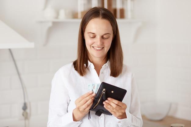 Wewnątrz ujęcie bogatej kobiety w białej koszuli w stylu casual, pozującej w jasnej kuchni z czarnym portfelem w dłoni, liczącej swoje oszczędności przed pójściem na zakupy.