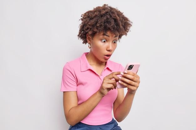 Wewnątrz ujęcie kobiety z kręconymi włosami patrzy zszokowanej na wyświetlacz smartfona czyta treść wiadomości reaguje na ofertę mobilną nosi różową koszulkę na białym tle nad białą ścianą