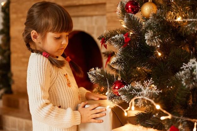 Wewnątrz ujęcie ładnej małej dziewczynki stojącej w pobliżu choinki, trzymającej ręce na pudełku prezentowym, kończącej dekorację choinki, ubranej w biały, ciepły sweter w stylu casual.
