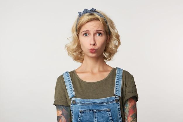 Wewnątrz ujęcie młodej wytatuowanej kobiety, z blond falującymi włosami, wygląda na smutno i zdenerwowaną na szaro