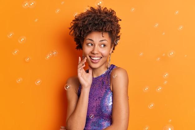 Wewnątrz ujęcie pięknej afroamerykanki, która uśmiecha się delikatnie, ubrana w modne ciuchy na randkę, ma nagie ramiona odizolowane na pomarańczowej ścianie latające bańki mydlane