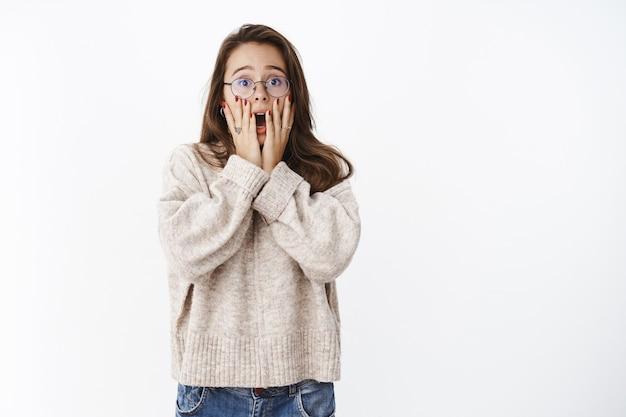 Wewnątrz ujęcie przerażonej, zszokowanej i zdumionej młodej kobiety w okularach i swetrze krzyczącej z potrząsanego zasłaniania rękami otwartych ust, przestraszonej i niepewnej, stojącej intensywnie nad szarą ścianą.