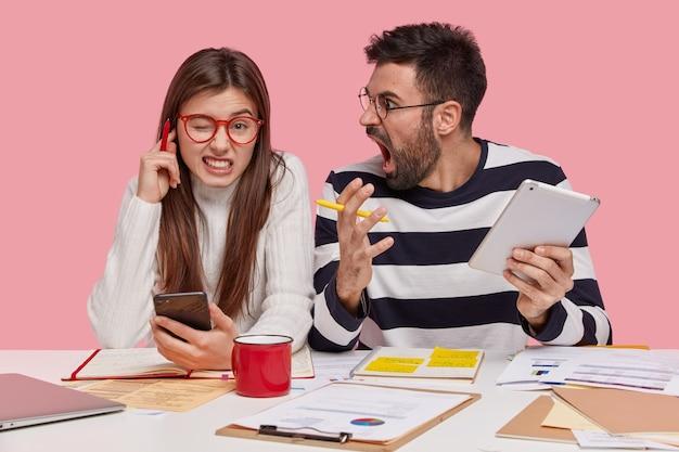 Wewnątrz ujęcie wściekłego mężczyzny, który krzyczy na stażystkę, trzyma touchpad, spraw, aby projekt działał razem, konsultował się zirytowana młoda kobieta zatyka uszy, słyszy uwagi szefa, odizolowana na różowej ścianie