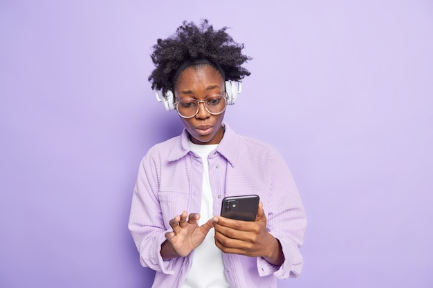 Wewnątrz ujęcie zaskoczonej, ciemnoskórej młodej kobiety z kręconymi włosami, która wygląda ze zszokowanym wyrazem twarzy na smartfonie
