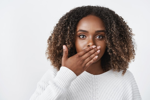 Wewnątrz ujęcie zaskoczonej i oszołomionej kobiety dyszącej z szoku, która zakrywa usta, oniemiała i zdumiona, wyglądająca na zmartwioną z przodu, reagującą na szokującą nieoczekiwaną sytuację nad białą ścianą