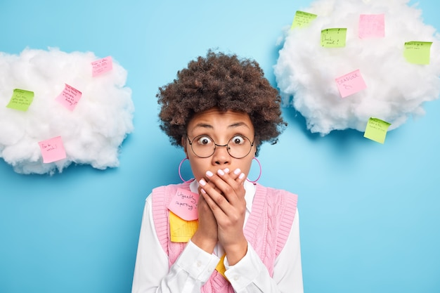 Wewnątrz ujęcie zszokowanej etnicznej pracowniczki, która trzyma ręce na ustach, pisze zadania i kreatywne pomysły na przyklejonym poście, zauważa, że termin nosi okrągłe okulary