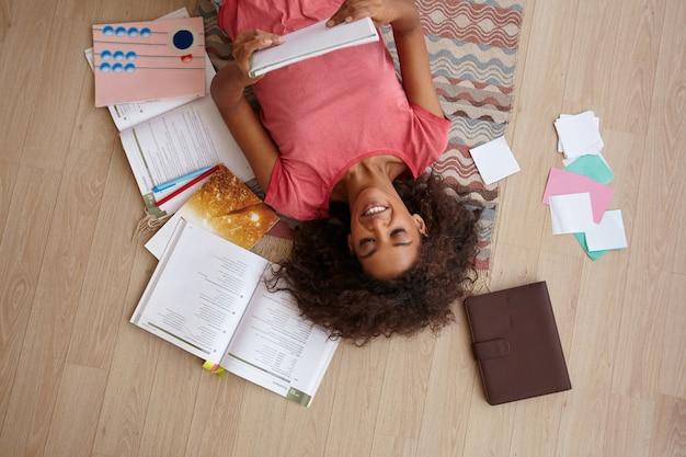 Wewnątrz widok z góry na uroczą młodą ciemnoskórą kobietę leżącą na podłodze z notatnikiem w rękach, przygotowującą się do egzaminów, marzącą o przyszłości, ubrana w różową koszulkę