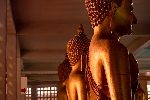 Wewnątrz wiele posągów buddy w rzędzie, siedzi w ciemnym miejscu.