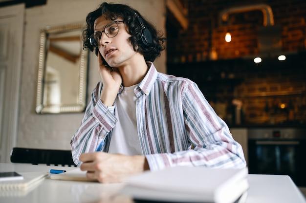 Wewnątrz wizerunek poważnego młodego mężczyzny z kręconymi włosami siedzącego w miejscu pracy z podręcznikami, zapisującego podczas słuchania wykładu przez bezprzewodowe słuchawki, uczącego się w domu. dystans społeczny