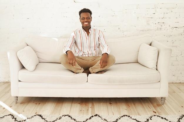 Wewnątrz wizerunek szczęśliwego, radosnego młodego ciemnoskórego mężczyzny siedzącego na wygodnej stylowej kanapie w salonie, trzymającego nogi skrzyżowane i szeroko uśmiechającego się, z zrelaksowanym, beztroskim wyrazem twarzy