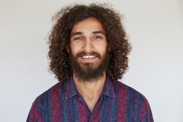 Wewnątrz zdjęcie atrakcyjnego, młodego, ciemnowłosego brodatego mężczyzny, który wygląda pozytywnie z czarującym uśmiechem, pokazując swoje białe, idealne zęby