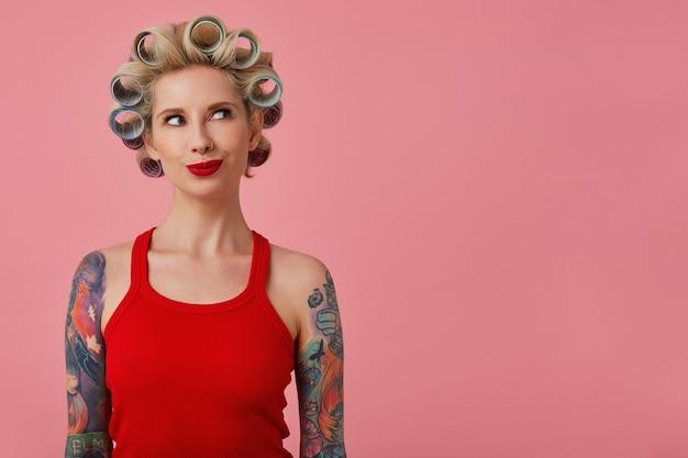 Wewnątrz zdjęcie atrakcyjnej młodej blondynki z wytatuowanymi rękami, mającymi lokówki na głowie i patrząc na bok z podekscytowaniem, ubrana w świąteczny makijaż, stojąc na różowym tle