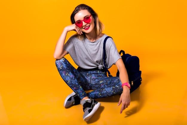 Wewnątrz zdjęcie dziewczyny w kolorowych legginsach i modnej koszuli siedzi na podłodze. studio portret stylowej młodej kobiety w butach sportowych, pozowanie na żółtym tle i trzymając plecak.