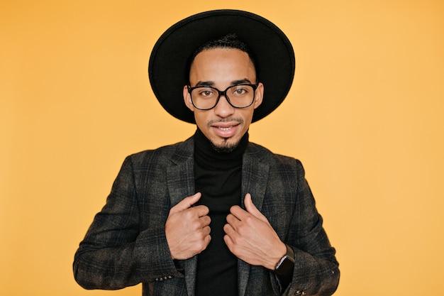 Wewnątrz zdjęcie fascynującego afrykańskiego młodego mężczyzny nosi stylowy zegarek na rękę. czarny facet w okularach pozuje z delikatnym uśmiechem.