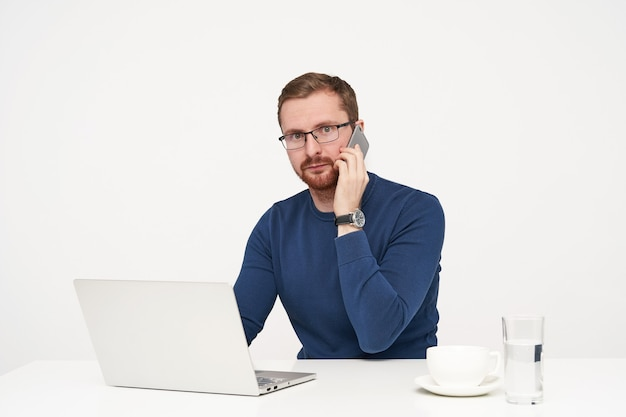 Wewnątrz zdjęcie młodego brodatego jasnowłosego biznesmena, trzymając telefon komórkowy w uniesionej ręce, patrząc zaskoczony na aparat, siedząc na białym tle