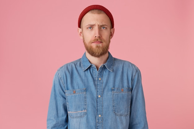 Wewnątrz zdjęcie młodego faceta w czerwonym kapeluszu z czerwoną brodą wygląda na smutnego, zdenerwowanego, zakleszczonego mężczyznę, niezadowolonego z czegoś, wyraża smutek melancholijnie, nosi modną dżinsową koszulę, na białym tle