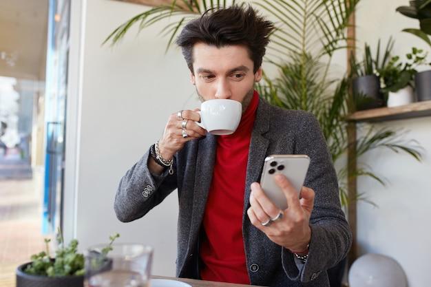 Wewnątrz zdjęcie młodego, ładnego brązowowłosego mężczyzny ubranego w eleganckie ubrania, popijającego kawę w miejskiej kawiarni, trzymającego smartfon w uniesionej dłoni i pozytywnie wyglądającego na ekranie