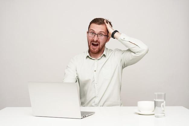 Wewnątrz zdjęcie młodego pobudzonego brodatego mężczyzny ubranego w białą koszulę, ściskającego głowę z podniesioną ręką i patrzącego ze zdumieniem w kamerę, pozującego na białym tle