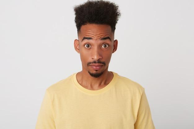 Wewnątrz zdjęcie młodego zdumionego, krótkowłosego, nieogolonego faceta o ciemnej skórze, unoszącego z zaskoczeniem brwi