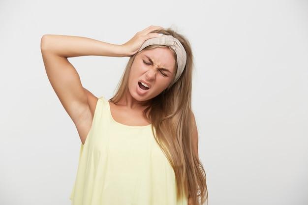 Wewnątrz zdjęcie młodej blondynki z naturalnym makijażem trzymającej dłoń na głowie i mającej zamknięte oczy, marszcząc brwi z niezadowoloną twarzą, odizolowane na białym tle
