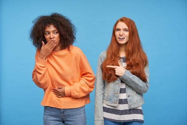 Wewnątrz zdjęcie młodej brązowowłosej ciemnoskórej kobiety w pomarańczowym swetrze z dzianiny i dżinsach zakrywających usta i trzymającej rękę na brzuchu, pozującej nad niebieską ścianą ze zdezorientowaną rudowłosą damą
