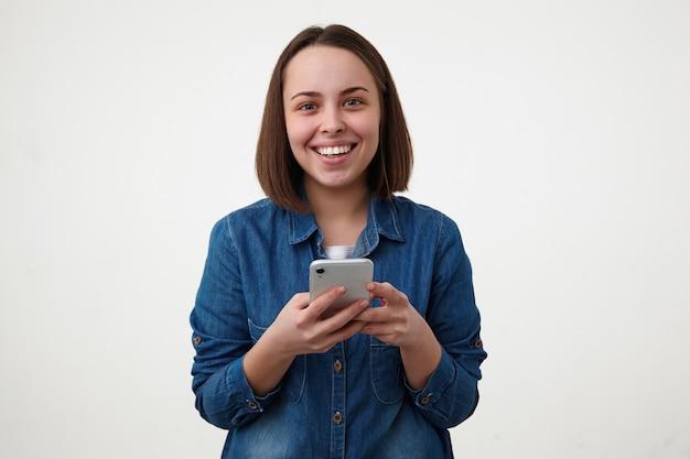 Wewnątrz zdjęcie młodej całkiem wesołej ciemnowłosej pani uśmiechającej się szeroko, patrząc z radością na aparat, trzymając telefon komórkowy, pozując na białym tle