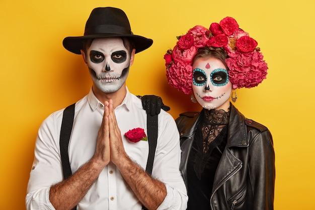Wewnątrz zdjęcie modlącego się upiornego mężczyzny z wizerunkiem zombie, trzymającego razem dłonie, poważna kobieta z wiankiem kwiatów wokół głowy stoi blisko, ma przerażający makijaż. halloween lub dzień zaduszny.