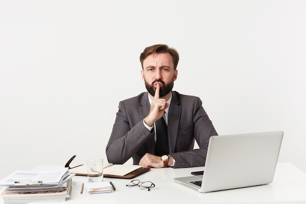 Wewnątrz zdjęcie poważnego młodego brodatego biznesmena pracującego w biurze z laptopem i notebookiem, siedzącego przy stole nad białą ścianą i podnoszącego rękę w geście ciszy