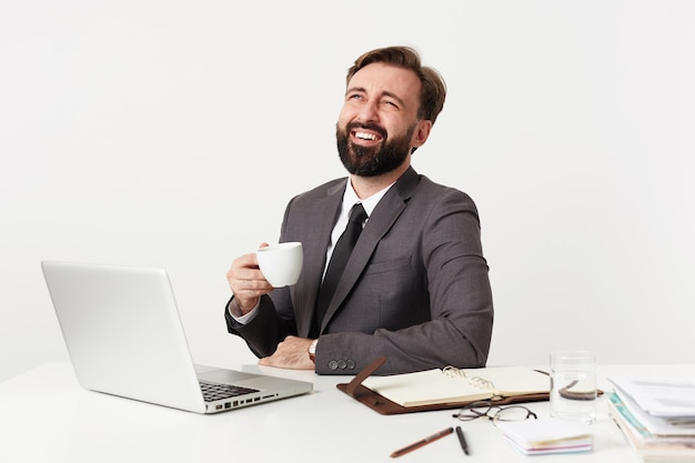 Wewnątrz zdjęcie radosnego młodego brodatego bruneta pracującego w biurze ze swoim laptopem, śmiejącego się radośnie podczas picia herbaty, noszącego szary garnitur i krawat na białej ścianie