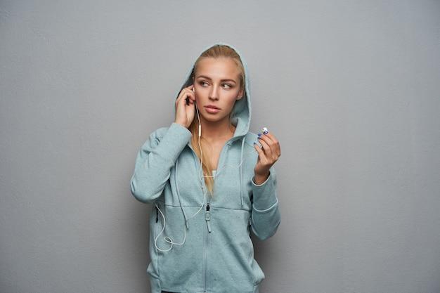 Wewnątrz zdjęcie sportowej młodej blondynki z przypadkową fryzurą ubraną w strój sportowy z kapturem, stojąc na jasnoszarym tle, wkładając słuchawki do uszu i patrząc na bok