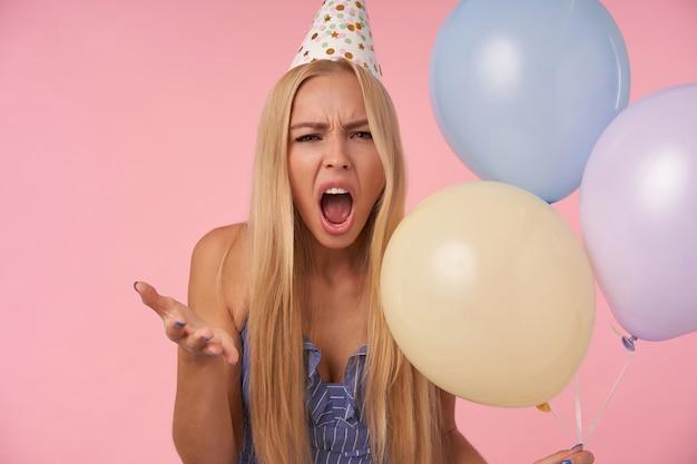 Wewnątrz zdjęcie surowej młodej blondynki unoszącej dłoń ze złością i patrzącej na aparat z szeroko otwartymi ustami, będącej w złym nastroju, pozującej na różowym tle z bukietem balonów z helem
