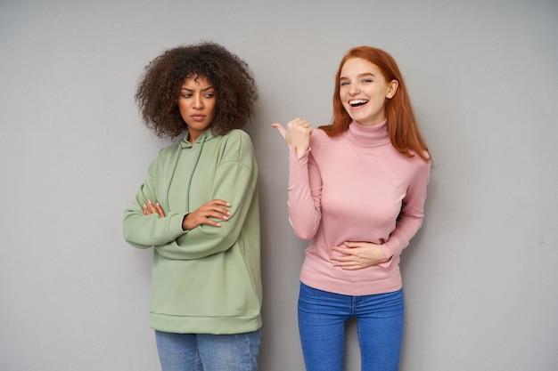 Wewnątrz zdjęcie szczęśliwej rudowłosej kobiety pokazującej z podniesioną ręką na jej surowym ciemnowłosym, kręconym ciemnoskórym przyjacielu i śmiejącej się radośnie, odizolowanej na szarej ścianie