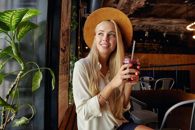 Wewnątrz zdjęcie uroczej ładnej blondynki w szerokim brązowym kapeluszu i białej koszuli siedzącej przy oknie w miejskiej kawiarni, patrząc na bok i uśmiechając się radośnie, mając przerwę na lunch w pobliżu biura
