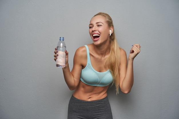 Wewnątrz zdjęcie uroczej szczęśliwej sportowej kobiety z fryzurą w kucyk, śmiejącej się radośnie i trzymającej butelkę wody, zadowolonej z wieczornego treningu, odizolowanej na szarym tle