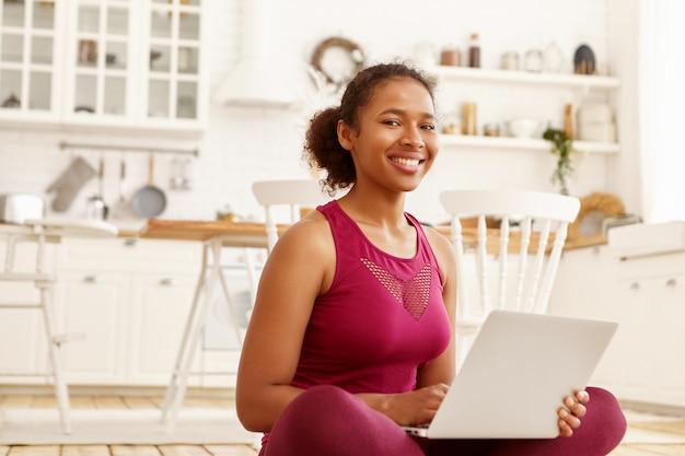 Wewnątrz zdjęcie uroczej wesołej młodej afrykańskiej kobiety w stroju sportowym siedzącej na podłodze w kuchni, trzymającej przenośny komputer, uśmiechającej się szeroko, oglądającej kurs wideo na pilates lub jogę online