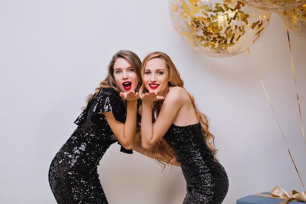 Wewnątrz zdjęcie wyrafinowanych dziewczyn z jasnym makijażem, pozujących razem. błogie panie ubrane w błyszczące czarne stroje wysyłające pocałunki na przyjęciu urodzinowym.