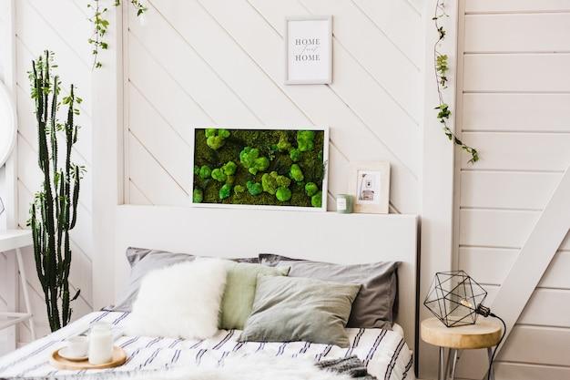 Wewnętrzna ściana świetlna z obrazem mchu, białych ścian, roślin, świec i ramek, łóżka, domu i komfortu