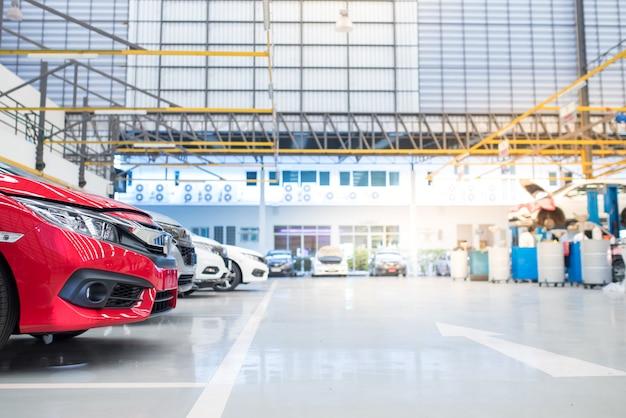 Wewnętrzne centrum pielęgnacji samochodów. elektryczny podnośnik do samochodów w serwisie umieszczony na posadzce epoksydowej w serwisie nowych samochodów