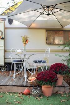 Wewnętrzne letnie patio z kwiatami w doniczkach oraz stołem i krzesłami na werandzie domu