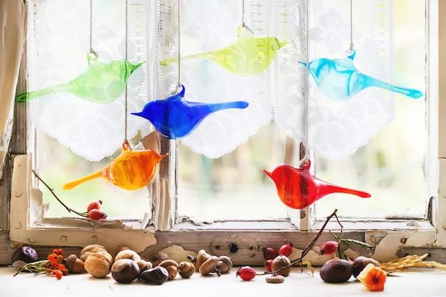 Wewnętrzne okno ze szklanymi ptakami i orzechami