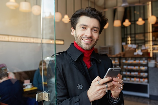 Wewnętrzne zdjęcie młodego czarującego brązowowłosego mężczyzny z modną fryzurą, patrzącego pozytywnie na aparat z szerokim uśmiechem, stojącego nad wnętrzem kawiarni z telefonem komórkowym