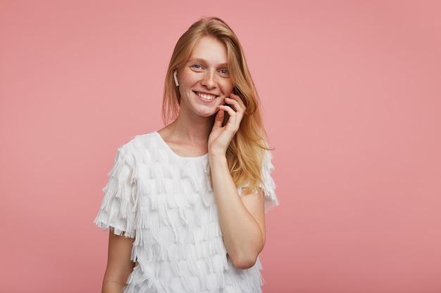Wewnętrzne zdjęcie pięknej pozytywnej młodej kobiety z lśniącymi włosami dotykającymi jej twarzy uniesioną ręką i patrzącej wesoło na aparat z przyjemnym uśmiechem, stojącej na różowym tle