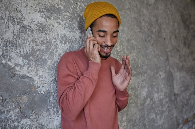 Wewnętrzne zdjęcie pozytywnego, ładnego, młodego ciemnoskórego mężczyzny z brodą, trzymającego telefon komórkowy w dłoni i dzwoniącego do przyjaciela, stojącego nad betonową ścianą z podniesioną ręką
